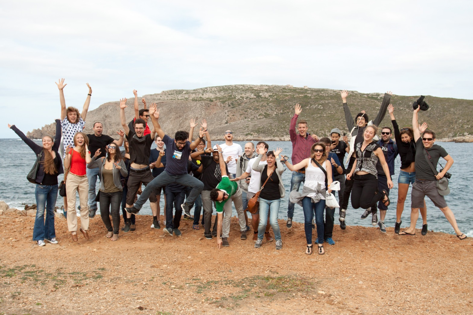 The team at Doist in Menorca in 2015. They are jumping into the air together.